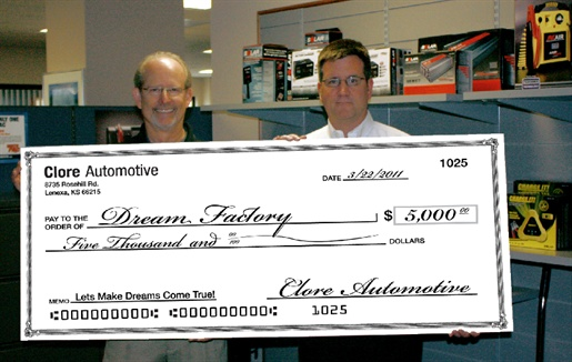 Jim O'Hara (right), Clore Automotive's vice president of marketing, presents the company's $5,000 donation to Ralph Apel, president of the Dream Factory.