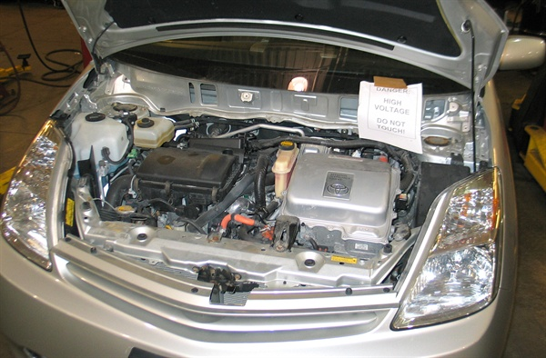Whenever servicing a hybrid, such as the Prius, it's a good idea to place a high voltage warning sign if the hood is left open. This reminds other techs not to touch any of the orange high voltage cables.