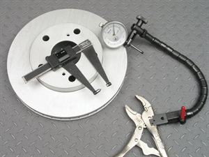 In order to conduct lateral runout and thickness measurements, a dial indicator and thickness gauge are mandatory. The dial indicator requires a mount that will attach rigidly to a non-moving surface, such as the flexible-locking mount shown here. While a common micrometer can be used to measure thickness, a specialty rotor thickness caliper such as the one shown here features one pointed anvil and an opposing flat anvil, for more accurate measurement.