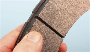 Center slots in the friction material (featured as a result of manufacturer testing and development) are often used to prevent friction material cracking where backing plate deflection is a concern, and to aid in self-cleaning.