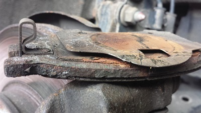 This brake pad has experienced drastic wear as a result of shims that have oxidized and separated, subjecting the pad to vibratory movement.