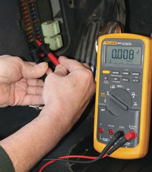 Measure the voltage drop across each fuse to find the circuit that's drawing current. One tenth of a millivolt (0.0001 volts) across a 30-amp fuse indicates 50 milliamps of current. This reading shows the control unit for the interior lights is drawing just over 1 amp through a 10-amp fuse.