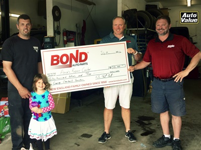 Aaron Belanger accepted the $50,000 check from Mark Mast, vice president of marketing for Bond Auto Parts, and Patrick Marshesseault, regional manager.