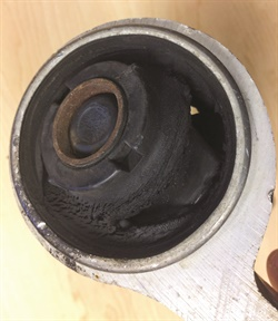 Note the torn and failed rubber bushing in the control arm that features a vertical bushing.