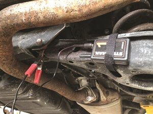 A wireless transmitter is attached to a control arm to monitor suspected bushing wear. Here the transmitter is secured with a Velcro strap.