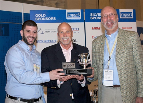 Alex Ragucci (left), CRP Automotive product manager, and Abe Garweg (right), CRP Automotive vice president of innovation, accept the Best Problem Solver Award for the Rein Automotive Water Pump Kit from Ira Davis (center), chairman of the Import vehicle Community, during the 2016 AAPEX Show.