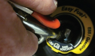 Apply compressed air in five short bursts onto the fuel tank filler pipe seal.