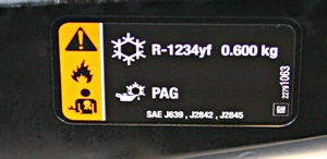 """On this new Malibu, the label is on the firewall. It indicates refrigerant type and quantity and the correct type of oil. Notice the """"flammable"""" icon."""