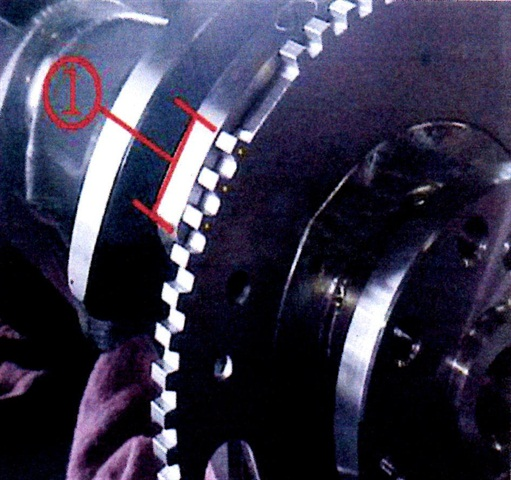 For reference, shown is the measurement for a properly-positioned reluctor wheel. From the end of the machined counterweight to the edge of the tooth should measure 25 to 26mm