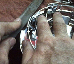 Lightly removing the chrome from the center cap fingers may eliminate the clicking noise complaint.