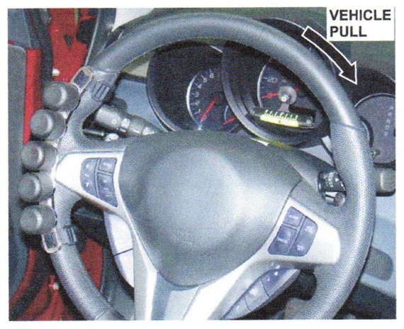 Attach the holding gauge to the side of the steering wheel that is opposite the direction of the pull.