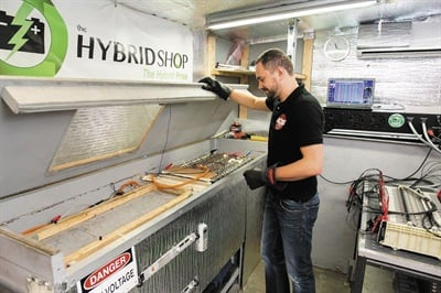 The Hybrid Shop's Martin Kruszelnicki performing battery reconditioning in a temperature controlled chamber. High voltage battery packs can often be reconditioned, offering an alternative to replacement.