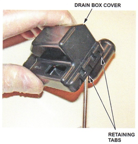 Use a small screwdriver to pry open the drain box cover.