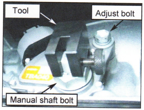 Loosen the adjusting bolt to the neutral start switch and install the adjustment tool.