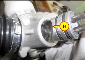 Install the support yoke with the concave end entering the housing, aligning the curve as shown (H).