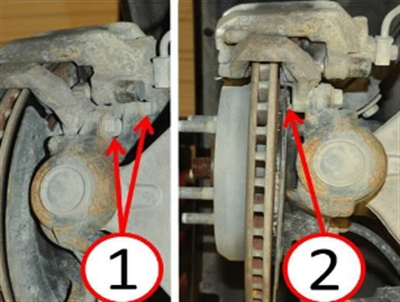 1) Caliper adapter mounting bolts; 2) Potential interference area between the bolts and dust shield.