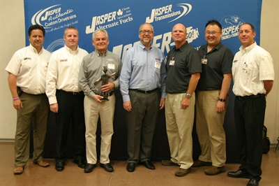 """Elgin Industries President Bill Skok, center, and National Sales and Marketing Director Rick Simko, third from right, receive the """"Elmo"""" award for service excellence during the recent Jasper Engines & Transmissions supplier conference."""