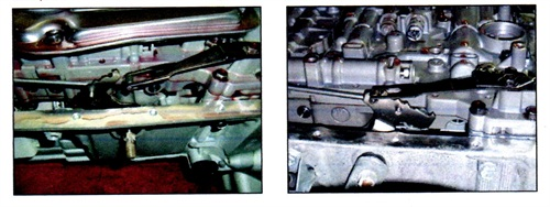 Left: Detent spring detached from the manual shift lever (transmission pan removed here for illustration). Right: Detent spring in place on the manual shift lever.