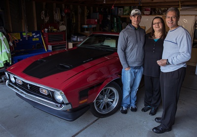 "Identified as ""George E.,"" the winner poses with his 1972 Mustang Mach 1 and his family."