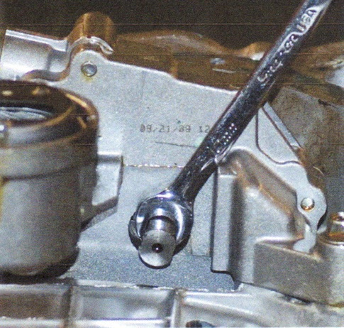 Close-up view of using a back-up wrench on the width-across-flat area of the oil pump shaft.