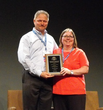 Pat Taylor (right), director ofcatalog services, accepts the Silver President's Award for Cardone's online catalog from John Strem.