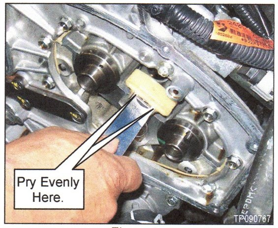 Figure 2. Remove the secondary timing chain tensioner shoes by prying as shown.