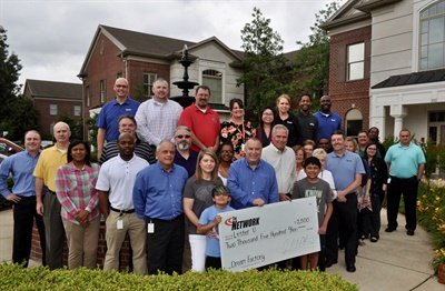 Network President David Prater and the Dream Factory's Brian Jeungling (both front row, right) presents Lester U. and his family with a $2,500 check that helped fund the 11-year-old's dream trip to Disney World.