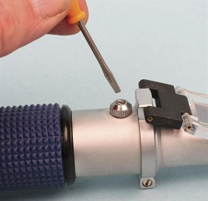 After popping off the rubber cap, use the supplied screwdriver to adjust the scale for zero calibration to pure water.