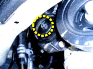 With the engine splash shield removed, access to the idler pulley nut requires the use of a crowfoot socket on your torque wrench.
