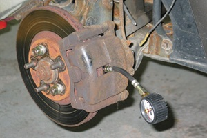 With the caliper remounted, the gauge hose hangs out of the caliper opening.