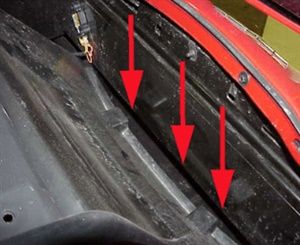 This is a picture of the upper radiator air baffle with a large gap that needs to be repaired. Repair the gap in the panel by making sure the retaining clips are properly seated or by installing new retaining clips. To access these clips, the vehicle must be raised and the three bolts securing the lower radiator air baffle to the bumper beam need to be removed.