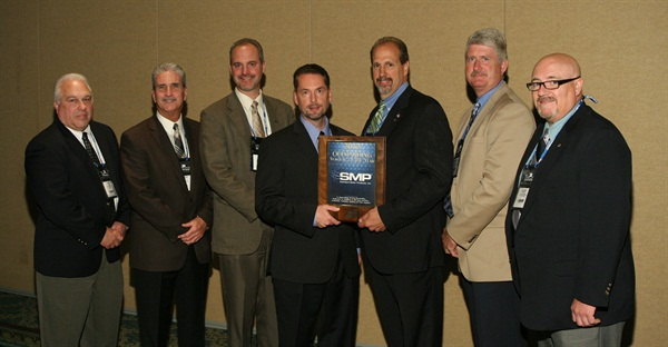 Bo Fisher, chairman of Federated Auto Parts (fourth from left) presents the Federated Outstanding Vendor of the Year award to Standard Motor Products (l to r):  Ken Wendling, Bob Kimbro, Matt Guden, Fisher, Bill Collins, Robert Frick and Alex Simmons.