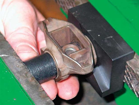 Using the Summit kit's presser (black tube) push the bearings and trunnion out of the rocker. The presser features a shallow counter bore that aligns to the stock bearing. Summit's specialty fixture on a bench vise is shown here. Push the old trunnion completely out of the rocker along with both OE bearings.