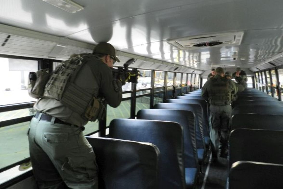 SWAT team members sweep a school bus after the live-action event that simulated a response to an...