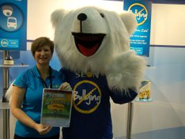 Seon's Lori Jetha and mascot display one of the winners of the company's anti-bullying coloring...