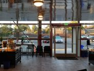 A view of the coffee bar. Bar stools line a 20-foot-long window. Charging ports are available...