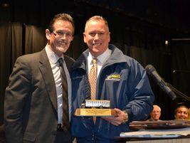 ASBC representative Leon Langley (left) presented the School Bus Champion Award to Elk Grove...
