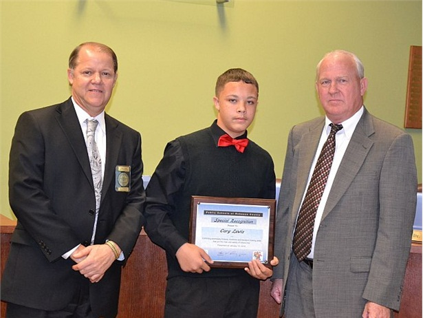 Cory Lewis, shown here with Public Schools of Robeson County school board members, was honored for stopping his school bus after it was in an accident and the bus driver had become unresponsive.