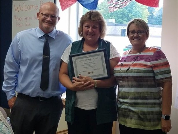 Helen Johnson, shown center, was honored by her company and the district she serves for helping a student's grandmother, who had fallen.