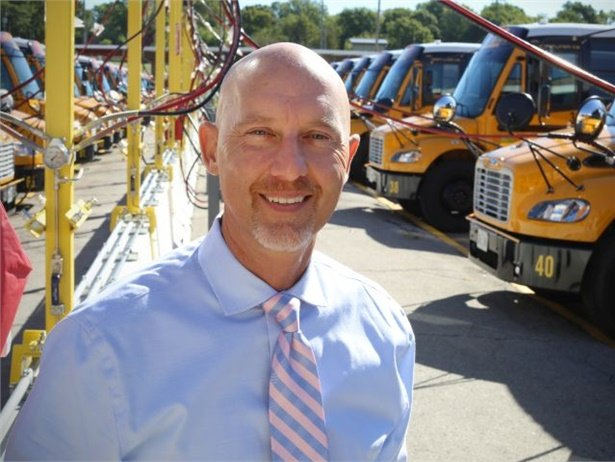 Lon Waterman, director of transportation for North Kansas City Schools, says that the move to alternative-fuel buses ties in with the district's overall environmental goals. In the background, new Thomas Built Saf-T-Liner C2 CNG buses are refueled at a time-fill station.