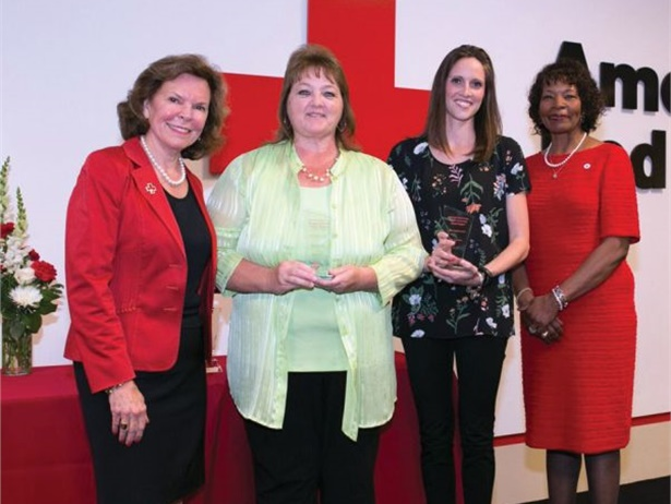 """The American Red Cross gave Petermann Bus the """"Good Neighbor Award"""" for transporting Cincinnati volunteers to distribute smoke alarms to families in need. Sue Prewitt (second from left), general manager for Petermann Bus, accepted the award. Photo courtesy American Red Cross"""