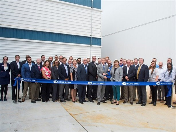 The school bus manufacturer'snew paint facility will provide paint coverage, minimize waste, and enhance efficiencies within Blue Bird's production line. Shown here is Phil Horlock, president and CEO of Blue Bird, along with some ofthe company's employees at the unveiling ceremony.