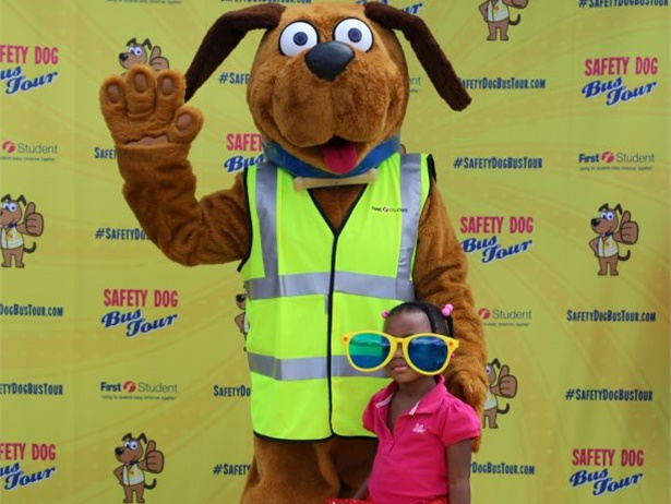 Students can pose for a photo with Safety Dog, the safety mascot for First Student, at the company's Safety Dog Bus Tour stops. Shown here is a student posing with Safety Dog during the 2016 tour.