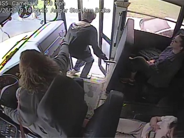 School bus video shows Samantha Call, a driver with Norwich (N.Y.) City School District, grabbing the student by his jacket as a vehicle speeds past the stopped bus. Screenshot from busvideo posted onthe district's Facebook page.