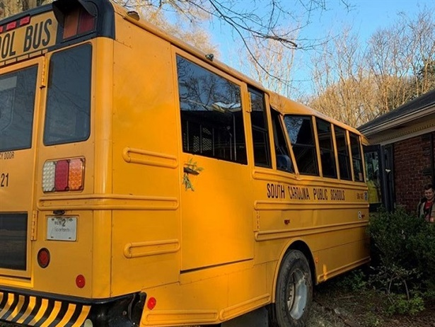 The South Carolina driver lost control of the bus, which ran off the side of the road. She overcorrected, and the bus spun around before hitting the tree and stopping against the house. Photo courtesy Spartanburg Fire Department