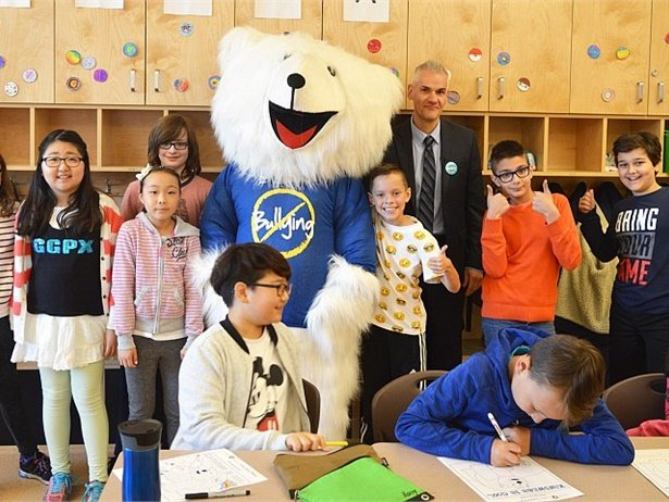 """""""Season of Kindness"""" contest entrants can share a photo or video of an act of kindness on their Facebook and Twitter pages to win a prize. Shown here is Buddy the Safety Bear, posing with a winner of Safe Fleet's 2016 anti-bullying coloring contest and his classmates."""