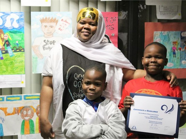 A 2017 United Against Bullying grant winner, St. Louis Public Schools, used the funds to expand its Safety Art Contest. Shown here, right, is the fourth place winner in the K-5 category, with his brother and mother.