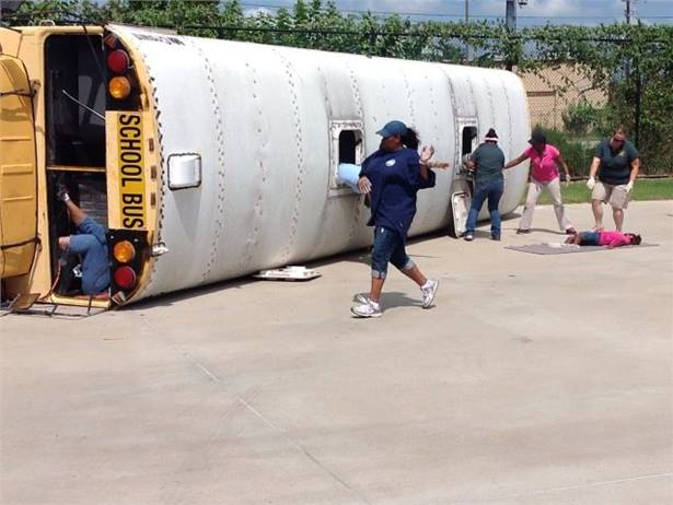 A Houston training event involves an older bus turned on its side and staged injuries, allowing bus drivers and attendants to practice their first aid training.