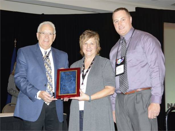 Kala Henkensiefken of Brainerd (Minn.) Public Schools won NAPT's Special Needs Transportation Award. She is seen here with Bud Fears (left) of Q'Straint/Sure-Lok, the award sponsor, and Minnesota state director Brian Reu, who nominated Henkensiefken.