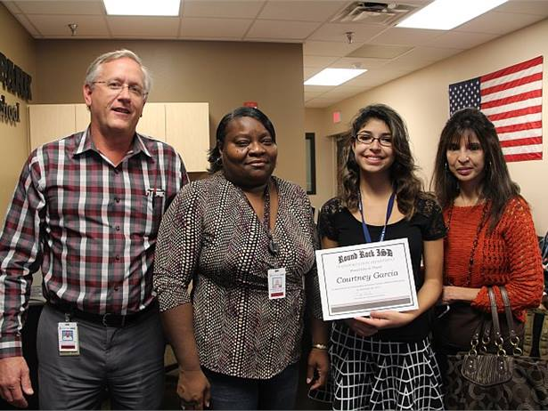 Courtney Garcia was recognized for her quick actions to help her bus driver, who became unresponsive while suffering a medical emergency. Shown here from left are Transportation Director Fritz Klabunde, the bus driver, Garcia, and Garcia's mother, Anita Garcia.